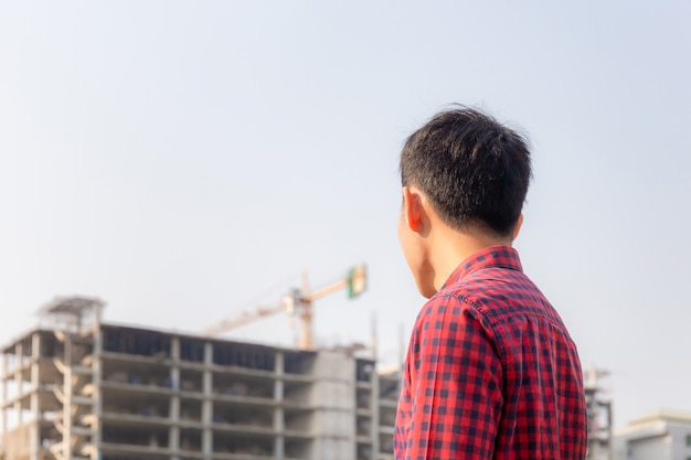 Engineer man checking and planning project at construction site, man looking into the building site