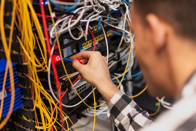 Engineer man connecting the optical fiber to ethernet switch