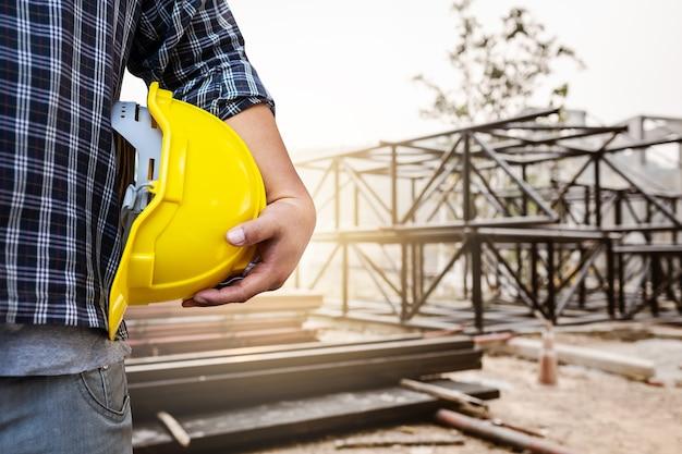 Инженер мужчина, держащий шлем со стальным фоном