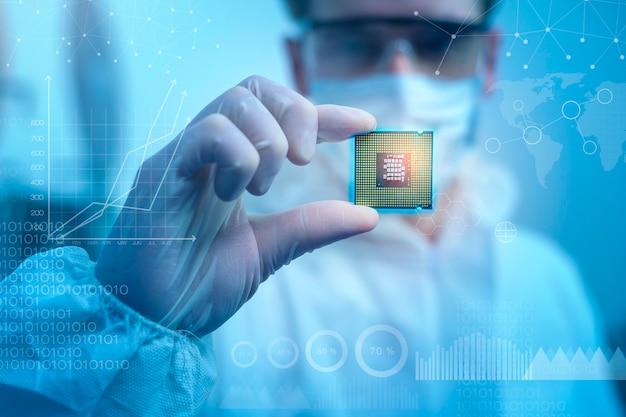 멸균 정장을 입은 엔지니어 남자는 현대 디자인 공장, 미래 및 인공 지능 개념에서 기호가 있는 microchip을 들고 있습니다.