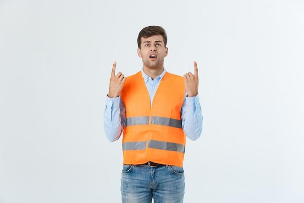 オレンジ色のヘルメットをかぶったエンジニアの男性が、スペースをコピーするために指を指しています。