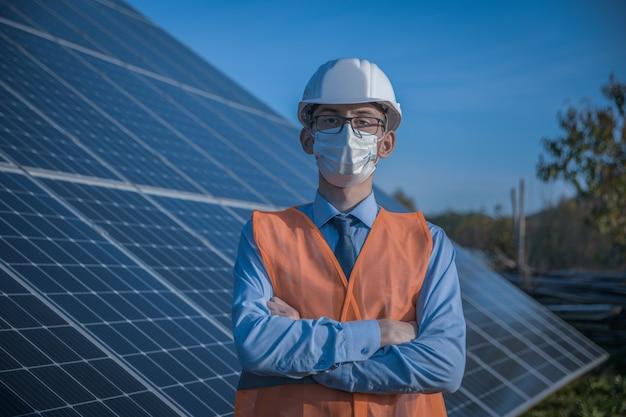 Инженер, человек в форме и маске, очках шлема и рабочей куртке на фоне солнечных батарей на солнечной станции. техник проверяет обслуживание.