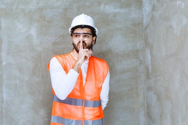 白いヘルメットと保護眼鏡をかけたエンジニアの男性が落ち着いていてほしいと頼んでいます。