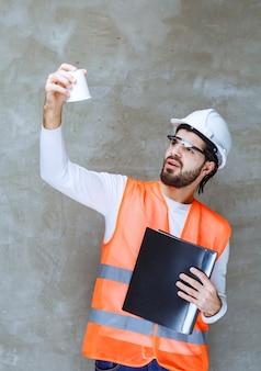 白いヘルメットと黒いフォルダーを保持し、彼のカップを覗き込んでいる保護眼鏡のエンジニアの男。