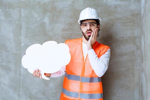Инженер в белом шлеме и защитных очках держит информационную доску формы и выглядит смущенным и напуганным.