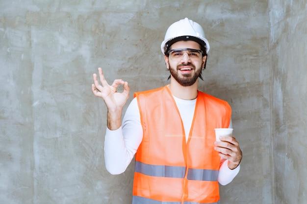 白いヘルメットと保護眼鏡のエンジニアの男は、飲み物のカップを保持し、楽しみのサインを示しています。