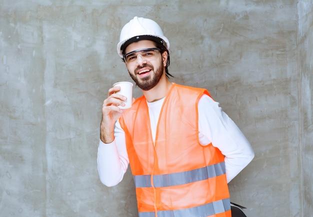 白いヘルメットと飲み物のカップを保持している保護眼鏡のエンジニアの男。