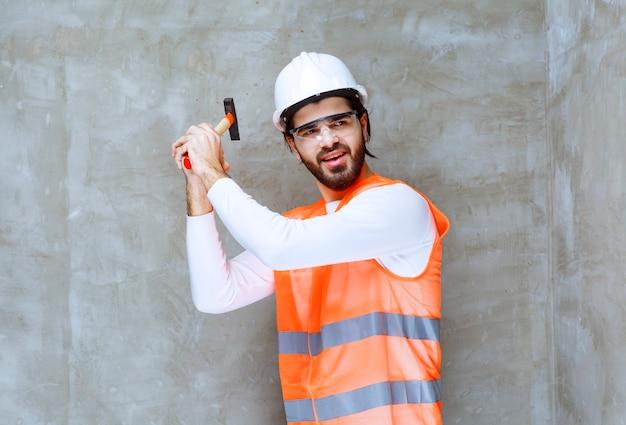 白いヘルメットと木製の斧を保持し、壁に釘を打つ保護眼鏡のエンジニア男。