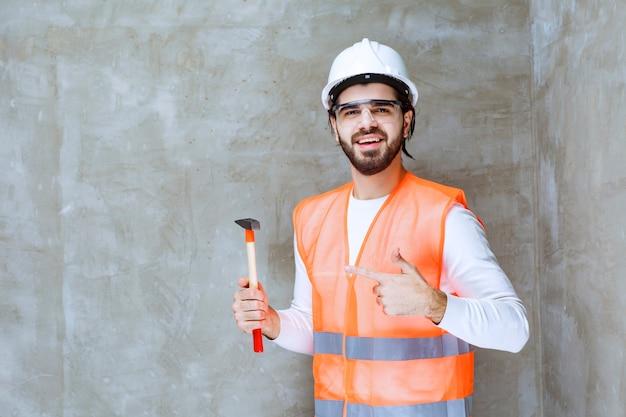 白いヘルメットと木製の斧を持って何かを指している保護眼鏡のエンジニアの男。