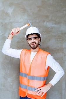白いヘルメットと木製の斧を保持している保護眼鏡のエンジニアの男。