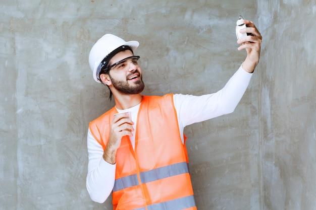 白いヘルメットと目覚まし時計と飲み物を保持している保護眼鏡のエンジニアの男。
