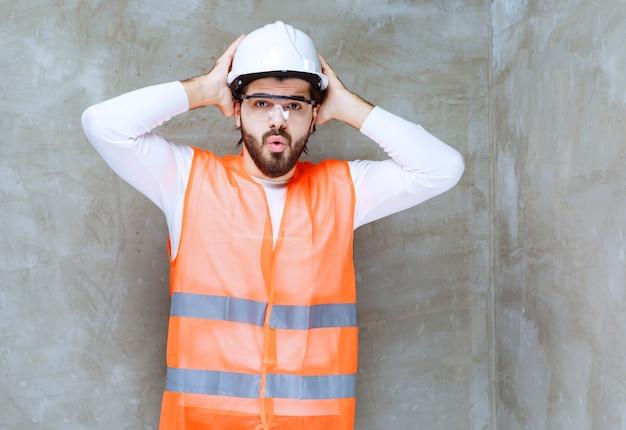 흰색 헬멧과 그의 머리를 잡고 보호 안경을 쓴 엔지니어 남자는 무서워하고 겁에 질려 보입니다.