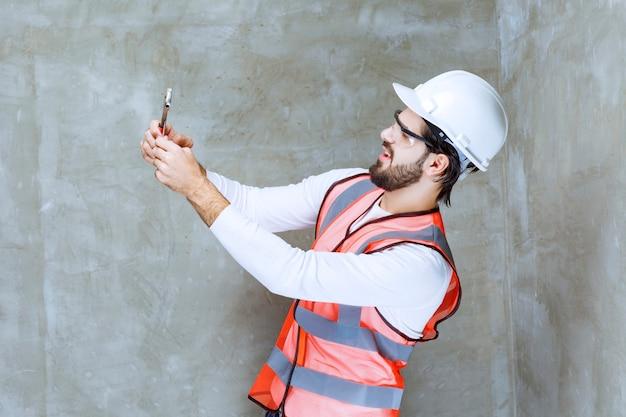 白いヘルメットと金属レンチを保持している保護眼鏡のエンジニア男。