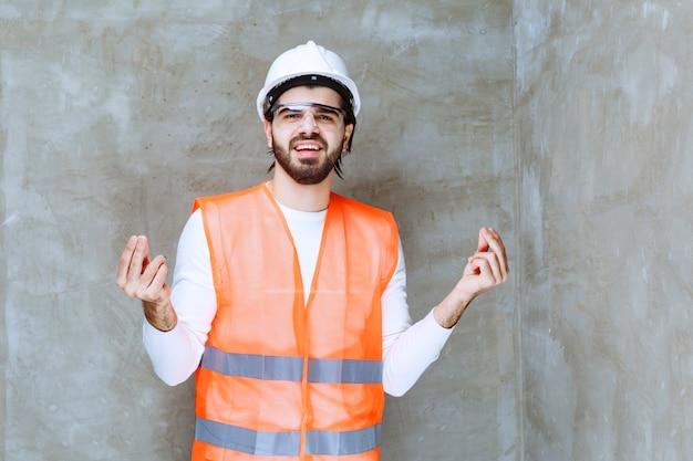 製品の品質を意味する白いヘルメットと保護眼鏡のエンジニアマン。