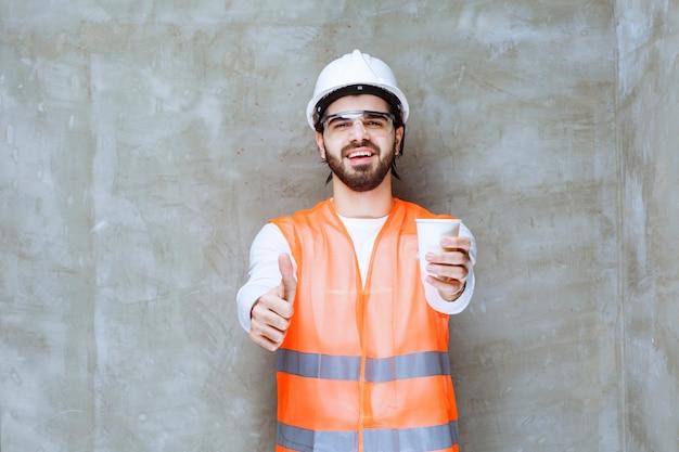 白いヘルメットと保護眼鏡をかけたエンジニアの男性が、パートナーに飲み物を提供しています。