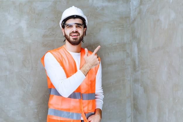 白いヘルメットと保護眼鏡をかけたエンジニアの男性が、同僚または脇の何かを指しています。