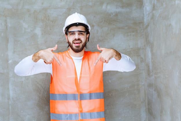 白いヘルメットと下の何かを指している保護眼鏡のエンジニアの男。