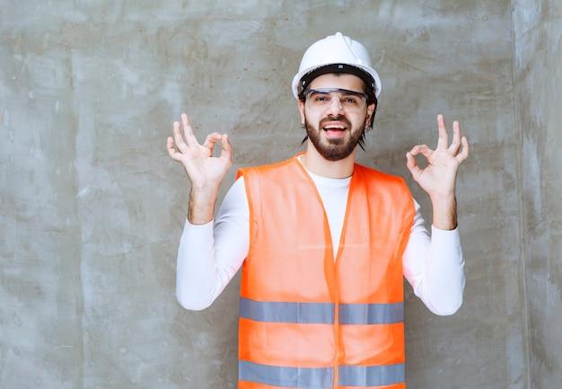 Человек инженера в белом шлеме и защитных очках показывает знак одобренной руки.