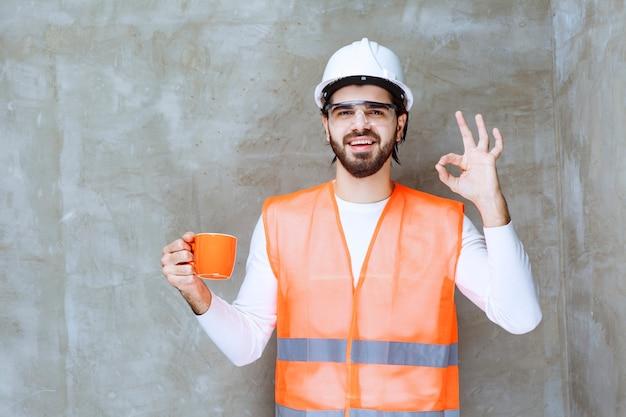 オレンジ色のマグカップを持って飲み物の味を楽しんでいる白いヘルメットのエンジニアの男。