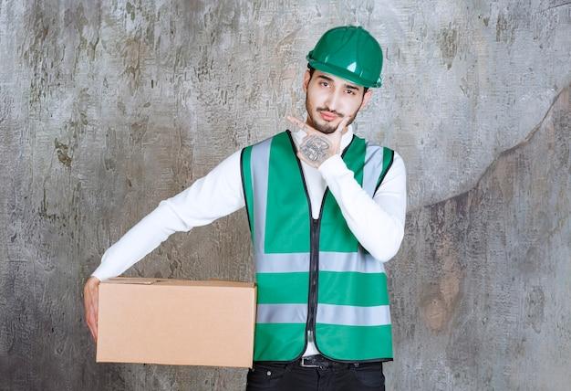 段ボールの小包を保持し、思慮深く見える黄色の制服とヘルメットのエンジニア男。