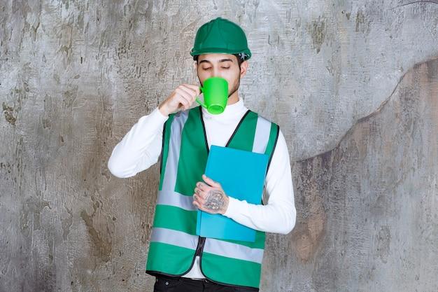 緑のコーヒーマグと緑のフォルダーを保持している黄色の制服とヘルメットのエンジニアの男。