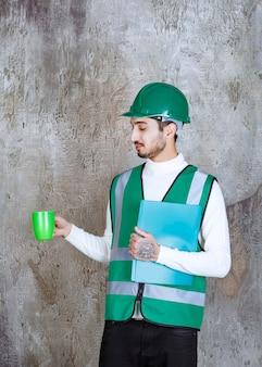 Инженер в желтой форме и шлеме держит зеленую кофейную кружку и зеленую папку