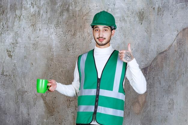 緑のコーヒーマグを持って製品を楽しんでいる黄色い制服とヘルメットのエンジニアの男。