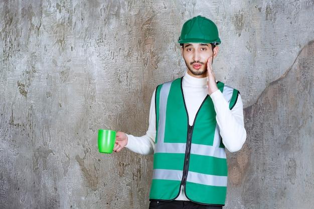 黄色い制服を着たエンジニアの男と緑のコーヒーマグを持ってヘルメットをかぶって驚いたように見えます。