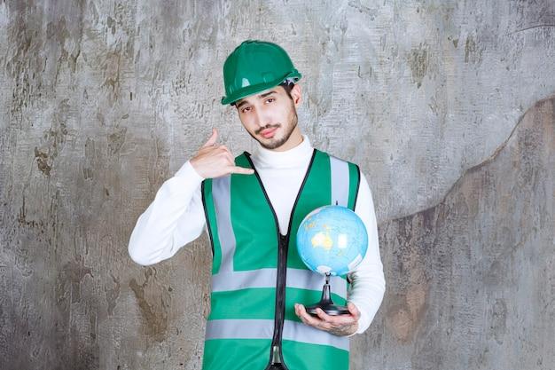 Инженер в желтой форме и шлеме держит глобус и просит звонка.