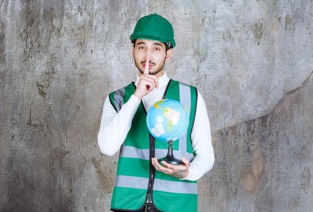 黄色い制服とヘルメットをかぶったエンジニアの男が世界の地球儀を持って沈黙を求めています。