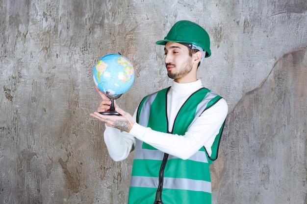 노란색 유니폼과 헬멧을 쓴 엔지니어 남자는 세계 지구본을 들고 그 위에 장소를 검색합니다.