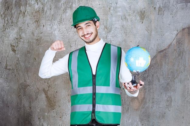 黄色のユニフォームとヘルメットのエンジニアの男は、世界の地球儀を保持し、肯定的な手のサインを示しています。