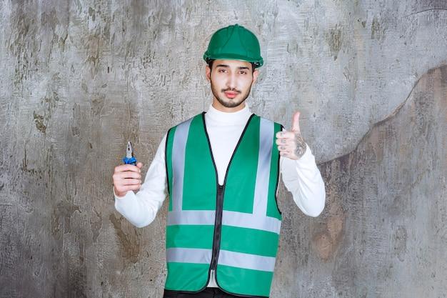 Инженер в желтой форме и шлеме держит синие плоскогубцы для ремонта и показывает положительный знак руки.
