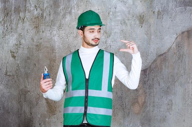 노란색 유니폼과 헬멧 수리를 위해 파란색 펜 치를 들고 개체의 크기를 보여주는 엔지니어 남자.