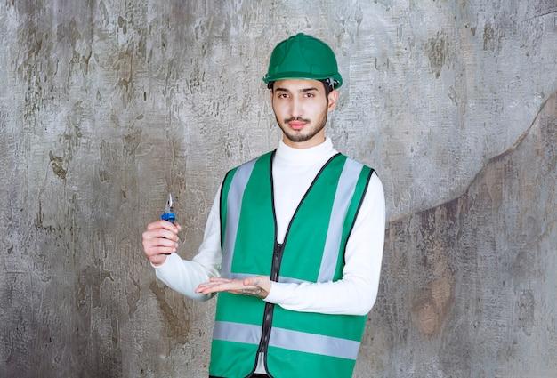 Инженер в желтой форме и шлеме держит синие плоскогубцы для ремонта