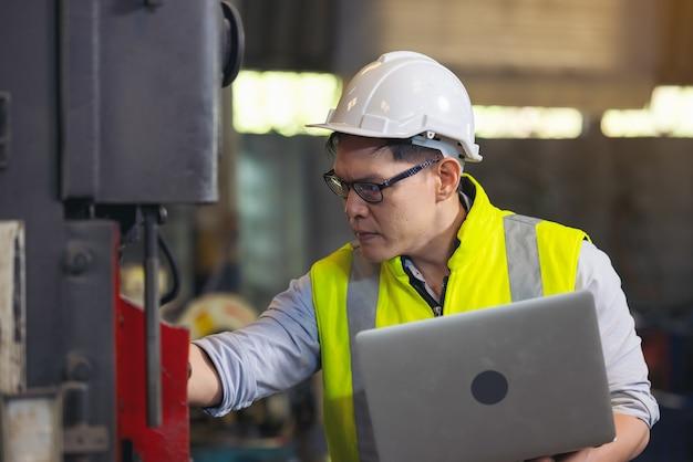 エンジニアマン、またはサージカルマスクを着用し、チェックにコンピューターノートブックを使用している技術者