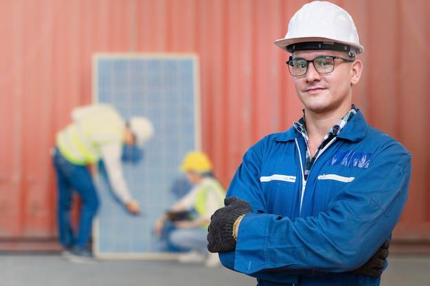 Человек-инженер, стоящий перед сотрудниками, проверяющими строительство возобновляемых источников энергии панели солнечных батарей