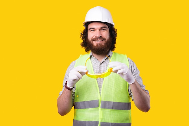 Engineer man wearing hard hat and holding yellow glasses for eye protection