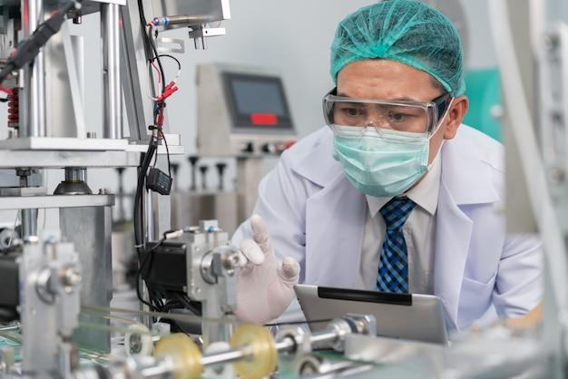 Engineer man wearing hygienic mask to protect coronavirus holding tablet checking machine at factory