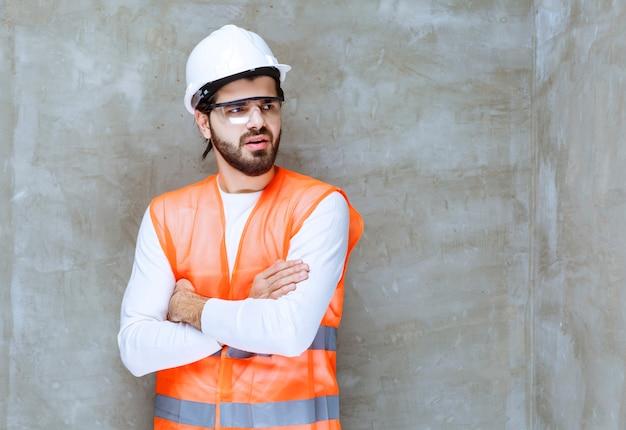 Uomo dell'ingegnere in casco bianco e occhiali protettivi incrociando le braccia e dando pose professionali.