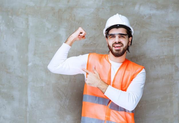 Uomo dell'ingegnere in casco bianco e occhiali protettivi che dimostrano i suoi muscoli del braccio.