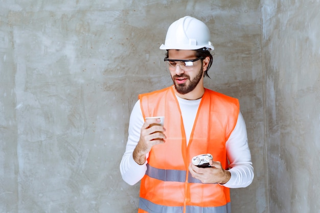 Engineer man in white helmet and protective eyeglasses holding an alarm clock and a cup of drink.