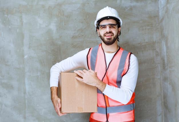 Uomo dell'ingegnere in casco bianco e occhiali protettivi che tengono un pacco di cartone.