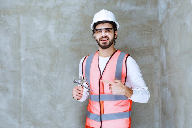 Engineer man in white helmet and protective eyeglasses holding metallic wrenches.