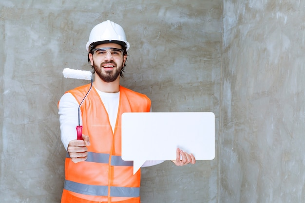 Engineer man in white helmet and protective eyeglasses holding a white rectangle info board and giving a trim roller to the colleague.