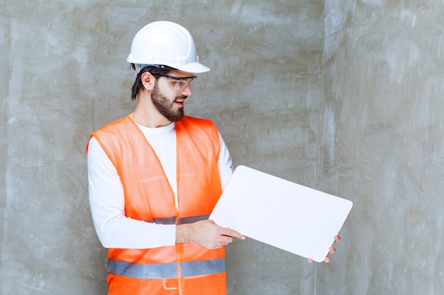 Uomo dell'ingegnere in casco bianco e occhiali protettivi che tengono una scheda informativa di rettangolo bianco.