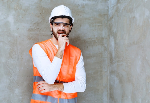 Engineer man in white helmet and protective eyeglasses looks confused and thoughtful.