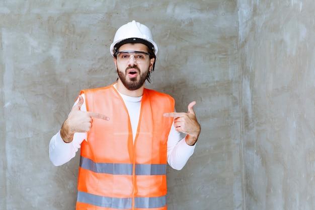 Uomo di ingegnere in casco bianco e occhiali protettivi che punta a se stesso.