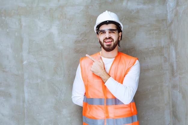 Uomo dell'ingegnere in casco bianco e occhiali protettivi che indicano il suo collega o qualcosa da parte.