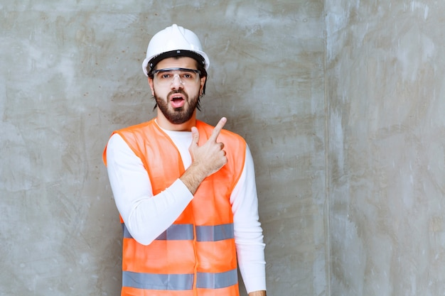 Engineer man in white helmet and protective eyeglasses pointing to something.
